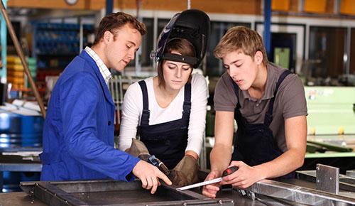 Ausbilder und seine zwei Auszubildende bei der Arbeit