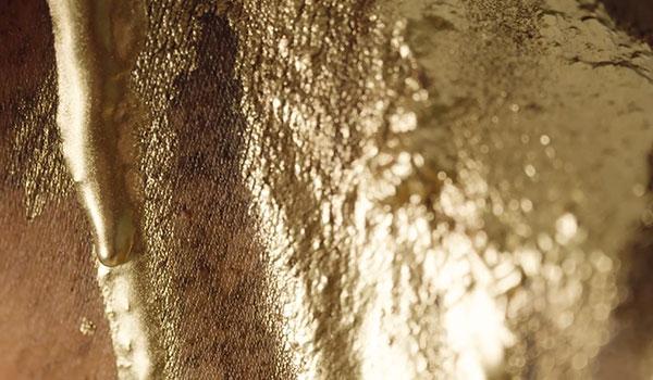 Goldene Farbe läuft über Haut